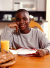 Boy doing homework with glass of orange juice