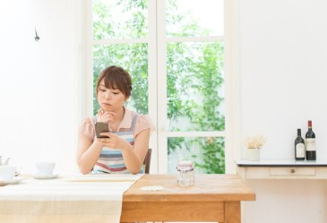 Asian woman sitting in kitchen on phone