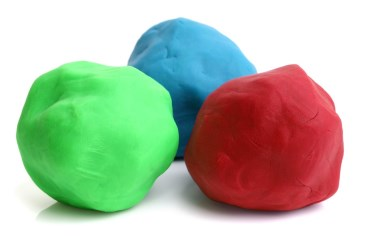 Three colorful balls on clay on white background