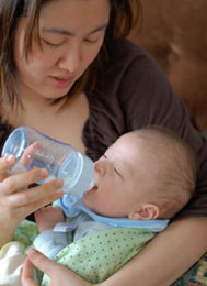 Mother bottle feeding child