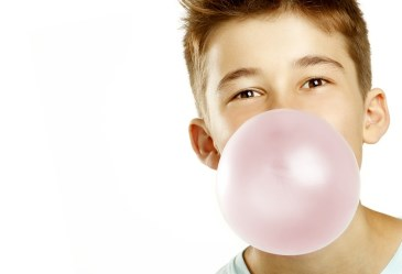 Boy blowing bubble of gum against white background