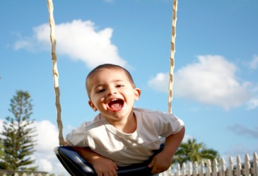 Happy boy on swingset in summer time
