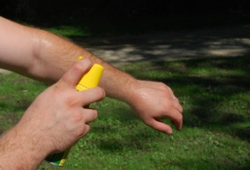 Man applying bug spray to arm