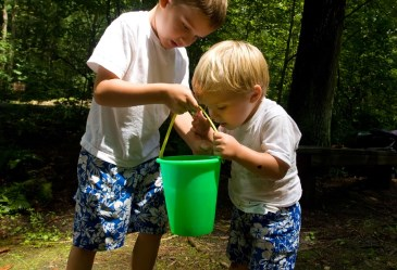Two boys playing outside with bucket of water