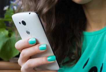 Close Up of Teen Holding Cell Phone with Painted Nails