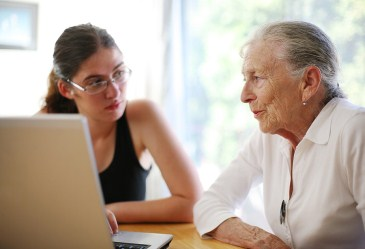 Young girl and elderly woman on the computer