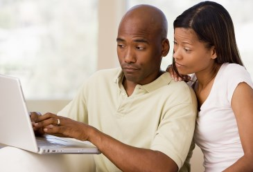 Couple looking annoyed on laptop