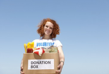 Young girl volunteer holding donation box smiling