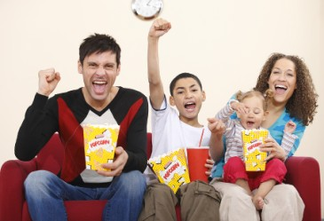 Happy family sitting on couch, cheeroing and eating popcorn
