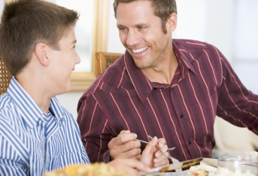 Father and son talking at dinner table