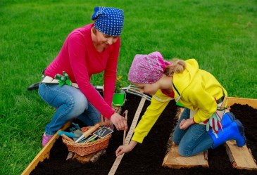 Mother and daughter planting seeds in garden
