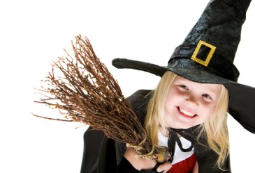 Young girl dressed up as a witch against a white backdrop.