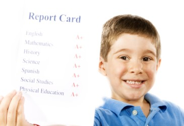 Happy boy holding up good report card