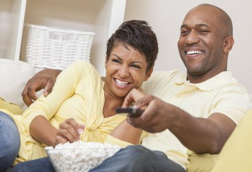Happy couple on couch eating popcorn
