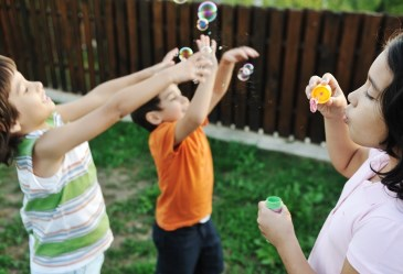 Happy kids blowing bubbles and playing in backyard