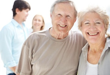 Close up of happy senior couple with grown children blurred in background