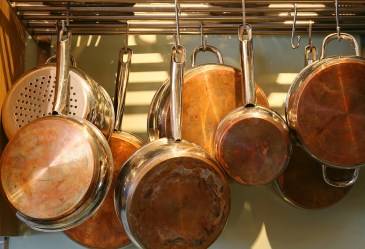 Copper pots and pans hung up on wall