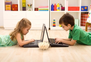Two kids using laptops with bowl of popcorn