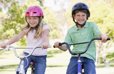 girl and boy ride bikes wearing helmets