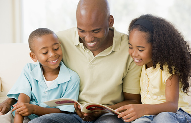 father reading to son and daughter