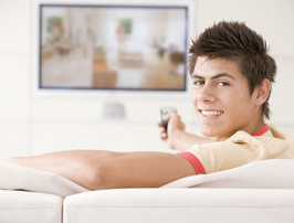Teen watching television on couch