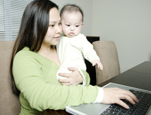 Mother at computer holding baby