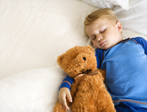 Boy sleeping with teddy bear