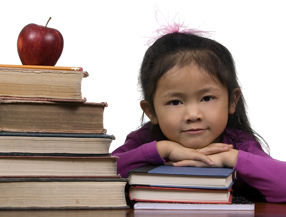 Young girl with apple and pile of books