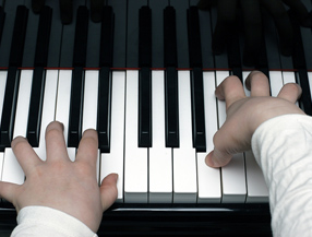 Child hands playing piano