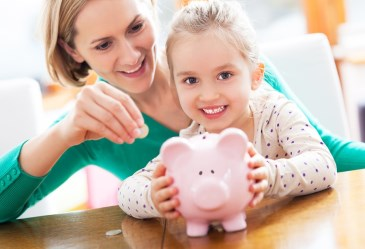 Mom and daughter putting change into piggy bank