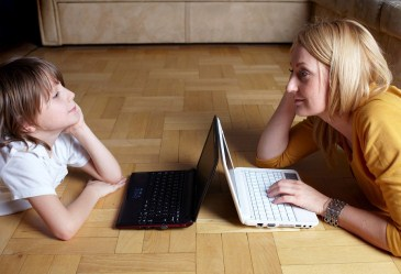 Mother and son facing each other using laptops