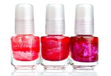 Row of nail polish bottles against white background