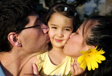 Close up of two parents kissing happy child's cheeks.