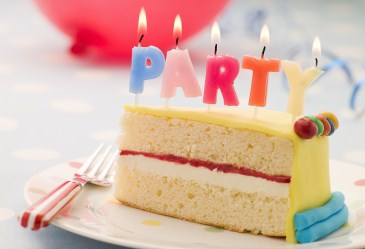 Slice of birthday cake with party candles