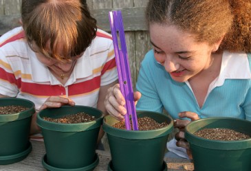 Two young girls planting seeds in pots