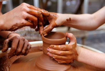 Two hands molding clay on pottery wheel