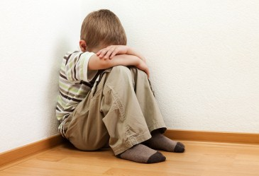Punished child sitting in corner with head in hands