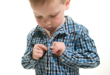 Young boy buttoning shirt and getting dressed against white background