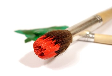 Paintbrushes with red and green paint against white background
