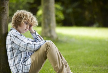 Sad child sitting against tree in park