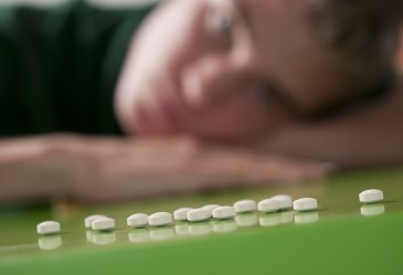 Row of white pills with teen arm in background
