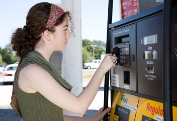 Teen paying for gas at pump with credit card