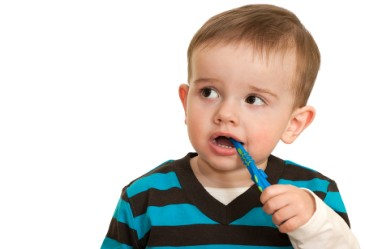 Close up o toddler brushing his teeth against white back drop.