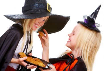 Two sisters dressed up as witches feeding each other Halloween biscuits.