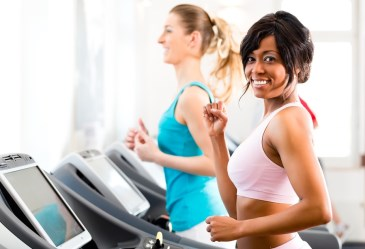 Happy woman running on treadmill