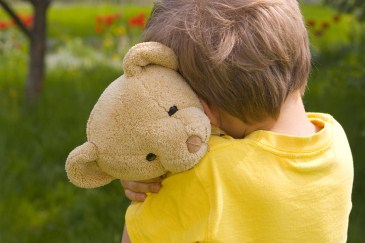 sensitive boy hugging bear
