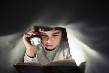 Summer camp essentials, boy reading with flashlight