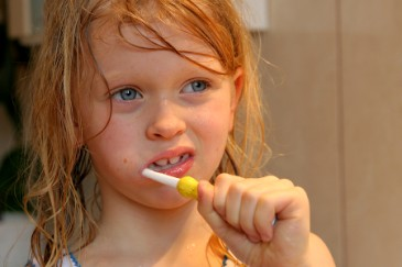 Summer camp essentials, girl brushing teeth with toothbrush