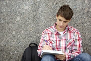 what colleges look for, male high school student writing essay