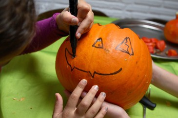 Halloween safety tip, child drawing on jack o lantern